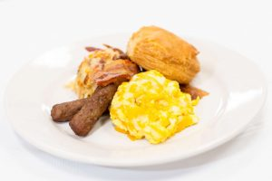eggs, sausage, buscuit and hash browns on a plate