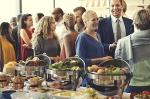 A crowd of people gathering around a catered corporate dinner.
