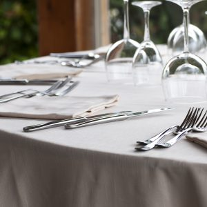 silverware and cutlery sets and glasses on a linen tablecloth