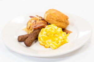 Rise and shine breakfast with scrambled eggs, sausage, potatoes, and a biscuit